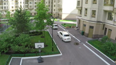 Two cars driving in the yard of multistorey houses, aerial view Stock Footage
