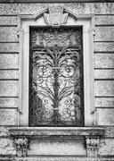 Window of an ancient Italian villa with artistic iron grill. Stock Photos