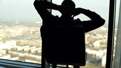 Silhouette of happy man turning round on the armchair in the office Stock Footage