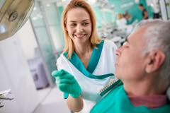 Female dentist shows to patient closest color of teeth for dentures Stock Photos