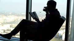 Silhouette of young man reading book on chair by window  Stock Footage