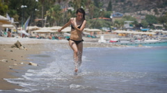 A young beautiful woman wearing black bikini running at a beach and laughing Stock Footage