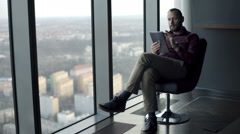 Young man sitting with tablet on the armchair by the window Stock Footage