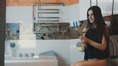 Young girl sit on toilet posing for selfie on smartphone. Monopod. Bathroom Stock Footage