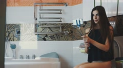 Attractive girl sit on toilet posing for selfie on smartphone. Monopod. Smile Stock Footage