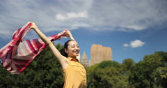 Asian woman in a park happy smile face waving scarf slow motion Stock Footage