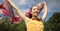 Asian woman in a park happy smile face waving scarf Stock Footage