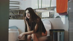 Young girl with long dark hair sitting on toilet talking on phone. Bathroom Stock Footage