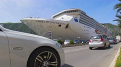 White cruise liner Costa Mediterranea docked in port of Kotor with car traffic Stock Footage