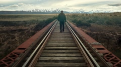 Man alone walking away on the train rails railroad Stock Footage
