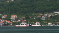 Two ferry boats cruising in Bay of Kotor in Lepetane, Montenegro Stock Footage