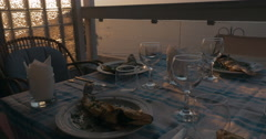 At sunset in city of Perea, Greece, dinner table served with cooked fish Stock Footage