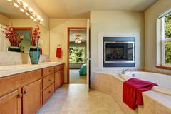Master bathroom with electric fireplace, large vanity cabinet with green vase Stock Photos