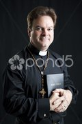 Priest With Rosary and Bible Stock Photos