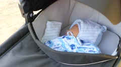 Hendheld shot of a gray pushchair with sleeping baby Stock Footage