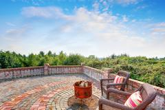 Paved brick patio of luxury house on Blue sky background. Two wicker chairs w Stock Photos