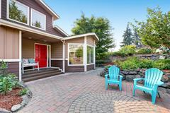 Suburban residential luxury house with paved brick patio. Red entrance door w Stock Photos