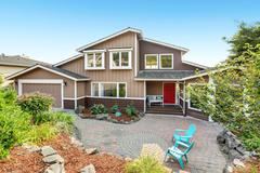 Suburban residential house with paved brick patio. Red entrance door with cov Stock Photos