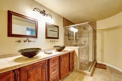 Bathroom with beige tile trim and glass shower. Wooden cabinet with vessel si Stock Photos