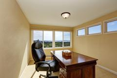 Upstairs home office interior design in yellow tones with nice wooden desk an Stock Photos