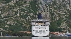 White cruise liner Norwegian Spirit turns around docked in Boka Kotor bay in Stock Footage