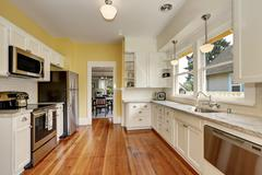 Kitchen interior with white cabinets, stainless steel appliances, yellow wall Stock Photos