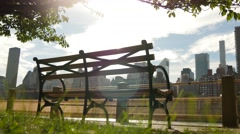 Empty bench in the city park. urban skyline view  Stock Footage