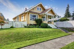 American craftsman home with yellow exterior paint and well kept front garden Stock Photos