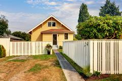 Backyard view of yellow siding craftsman house. White fence, green grass and  Stock Photos