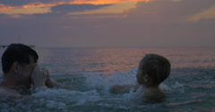 At sunset father with son swimming in sea of city Perea, Greece Stock Footage
