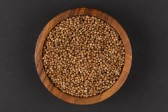 Coriander seeds in  small wooden bowl Stock Photos