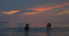 At sunset mother, father with their son swimming in sea of city Perea, Greece Stock Footage