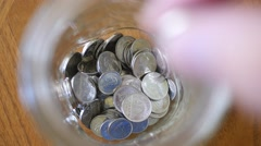 4K Closeup Saving Tip Jar Puting Money Coins Inside Stock Footage
