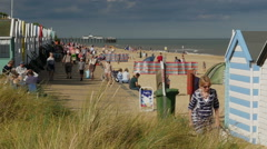 Beach Huts and tourists on the foreshore at Southwold Stock Footage