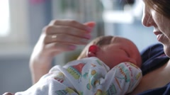 Young woman gently holding her baby and talking to him. Baby moving uneasily Stock Footage