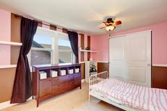 Minimalistic design of kid's bedroom  interior with pink accent walls. Iron b Stock Photos