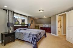 Interior design of grey tones bedroom with violet bed . Northwest, USA Stock Photos