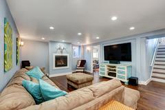 Pastel blue walls in basement living room interior. Large corner sofa with bl Stock Photos