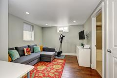 Sitting room interior with sport equipment and TV in the basement. There is a Stock Photos