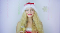 Smiling beautiful woman girl in Santa hat gives you a glass with champagne. kiss Stock Footage