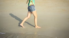Girl Walking Along the Beach in Shorts Barefoot. View Waist Down. Slow Motion Stock Footage