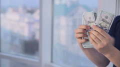 Man counting dollars at bright panoramic window. Money saving, economy, cash Stock Footage