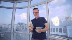 Man counting dollars at bright panoramic window. Money saving, economy, cash Stock Footage
