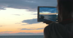 Woman takes photos of the beautiful scenery of the sea and evening sky with her Stock Footage