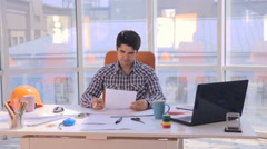Young busy businessman working with drawings, blueprints in a light, modern Arkistovideo