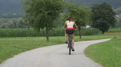 Young girl riding cycles on rural road Stock Footage