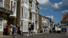 Visitors and tourists passing the Swan Hotel at the Market Place, Southwold Stock Footage