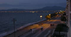 On the coast of city Perea, Greece on evening streets walking people Stock Footage