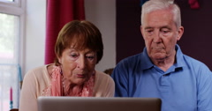 4k, Senior couple web browsing on their laptop from home. Stock Footage