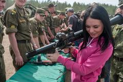 Girl considers the RPG-7 grenade launcher Stock Photos